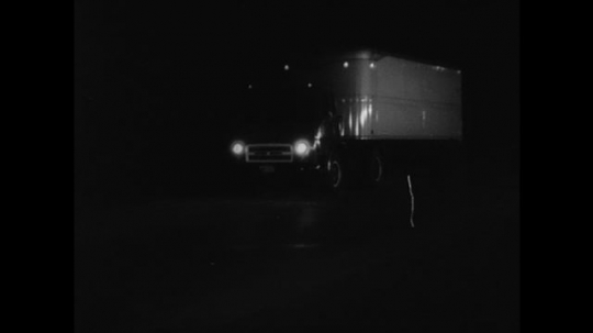 1950s: Semi-truck stops on dark road. Truck driver gets out of cab and lights flare. Truck driver rushes to cab and opens door.
