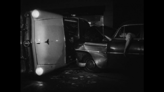 1950s: Car and police car are smashed together. Police officer hangs hurt out of window. Other driver wipes face, unhurt. Speeding car stops at light. Passenger gets out of car.