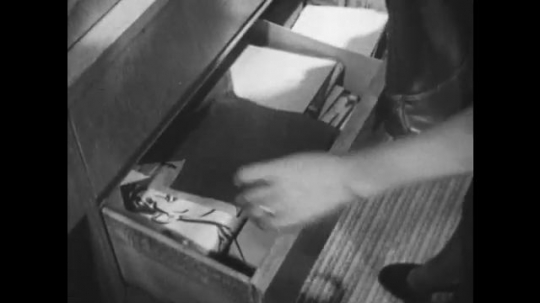 1950s: UNITED STATES: lady opens drawer. Lady leaves house with boy. Lady sits boy on bike