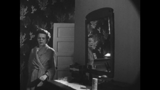 1950s: UNITED STATES: lady brushes hair in mirror. Lady looks at self