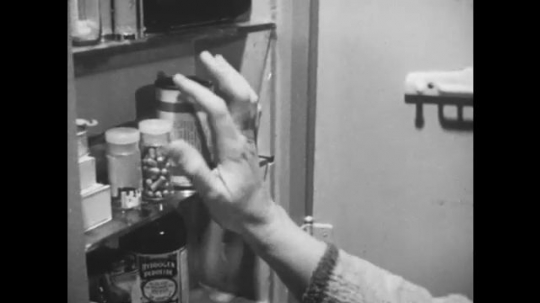 1950s: UNITED STATES: lady takes tablets from cabinet. Lady looks half asleep. Pills in hand