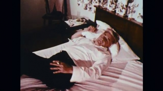 1950s: UNITED STATES: man rolls over in bed. Man falls asleep in bed. Man drops cigarette in bed. Bed catches fire. Fire fighters climb ladder to bedroom window