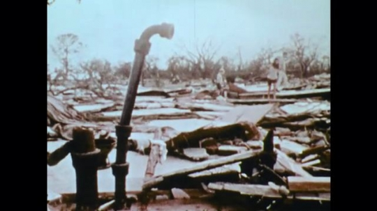1970s: men and women walk over remains of houses. men dig through wreckage and debris of building. crane hoists man on stretcher into air.