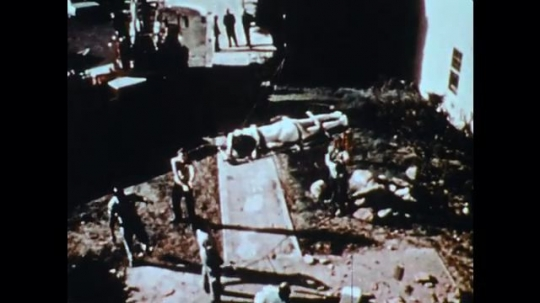1970s: crane lowers man on stretcher down to men on ground in debris. men and women carry hurt victims to ambulances and rescue centers in disaster zone.