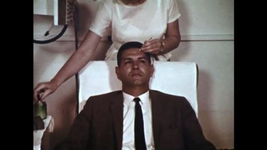 1960s: Zoom in, woman attaches electrode to man