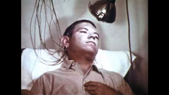 1960s: Man with electrodes attached to head, light flashes in man