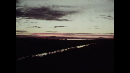 1980s: View of sunrise, river. Zoom out on scene. Tracking shot down river. Close up of man, zoom out to people in boat.