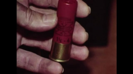 1980s: Close up, hands show shotgun shell, exploded shell.