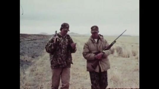 1980s: Men walk through field with guns.