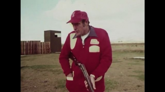1980s: Men on skeet range, men talk. Man aims at target.