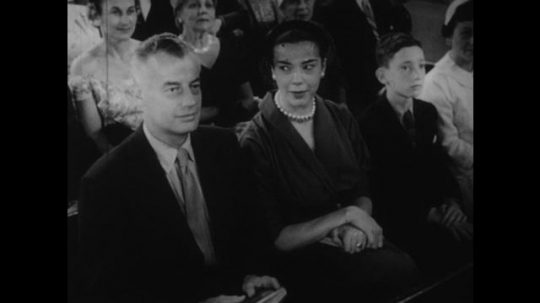 1950s: UNITED STATES: lady looks at man in church service. Young people lead church ceremony