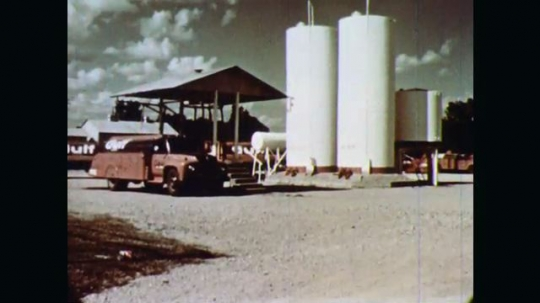 1970s: Truck is parked beside two tall holding tanks. Man wheels drum through warehouse filled with metal drums and a few cartons. Station attendant fills customer