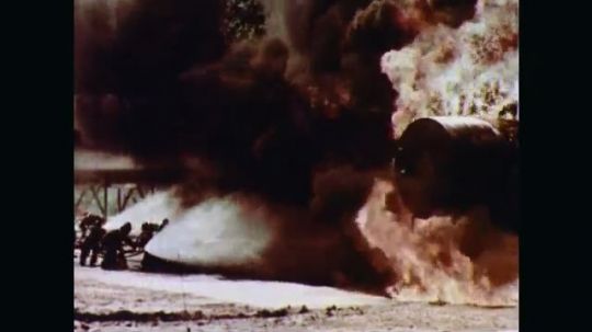 1970s: Fire and black smoke engulf a large horizontal cylindrical fuel storage tank. Firefighters advance on the fire with a wide coverage of spray patterns from their hoses as the flames grow.
