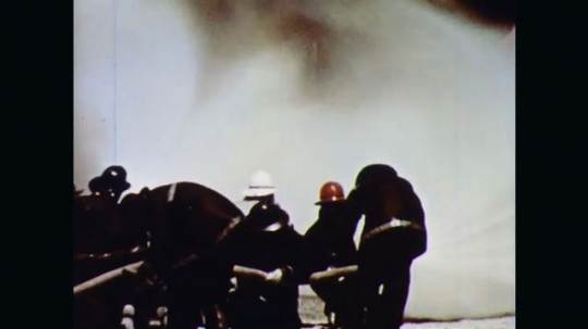 1970s: Fire and black smoke roar from a large horizontal cylindrical fuel storage tank. Firefighters crouch with hoses and slowly advance on fire. They train wide spray on fire to get closer to tank.