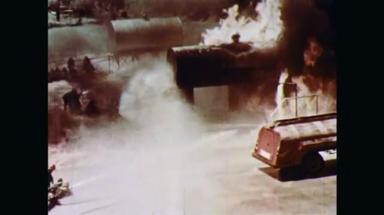 1970s: Fire and black smoke roar from a large horizontal cylindrical fuel storage tank. Firefighters crouch with hoses trained on fire. Firefighter closes tank valve and hose men slowly back away.