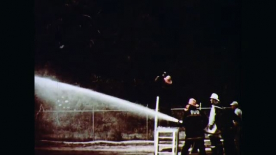 1970s: Firefighters spray hoses on flaming horizontal cylindrical storage tank. They spray the tank to cool it and push burning fuel down to ground. Firemen try to connect water line to tank pipe.