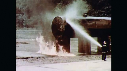 1970s: Firefighters spray hoses on remains of horizontal cylindrical storage tank fire. Water fed into supply line keeps fuel from feeding the fire and flames are extinguished.