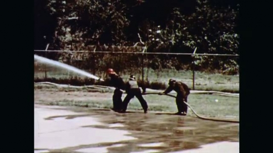 1970s: Fire and black smoke engulf a large horizontal cylindrical fuel storage tank. Firefighters on one side advance with high-pressure hoses on the flames.