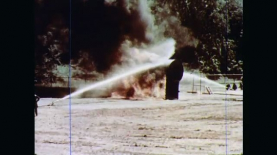 1970s: Unmanned fire hoses held in place by hose holders mounted in ground  spray water on burning tank. This setup can be used when tank is at risk of exploding.