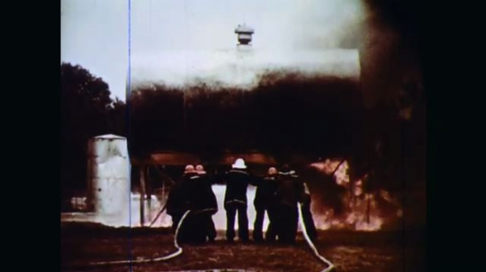 1970s: A horizontal cylindrical tank on a scaffoldlike mount is in flames. Firefighters stand closely together and train their hoses on both the tank and the scaffold support below it.