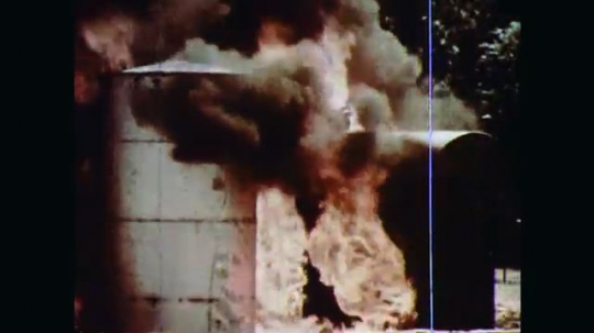 1970s: A vertical tank and a horizontal tank adjacent to each other outdoors are in flames. The vertical tank has top vent releasing steam. The horizontal tank