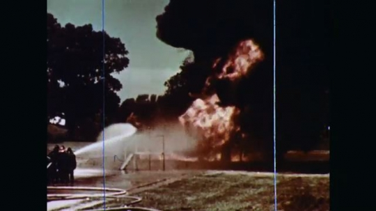 1970s: A vertical tank and a horizontal tank adjacent to each other outdoors are in flames with great clouds of black smoke. Firefighters train their hoses and advance on the growing fire.