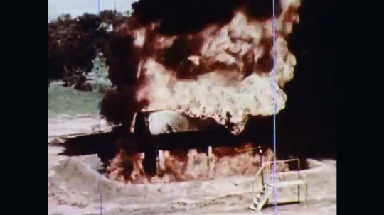 1970s: A vertical tank and a horizontal tank adjacent to each other outdoors are in flames with great clouds of black smoke. Unmanned hoses planted in ground spray the growing flames.