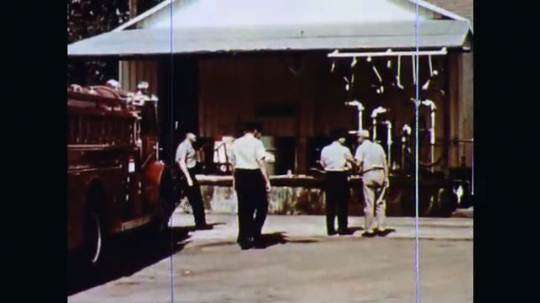 1970s: Worker shows team of fire inspectors the systems of pipes and valves in his plant. Worker and uniformed inspector walk on top of storage tanks. Inspector looks at valves and lifts hatch.