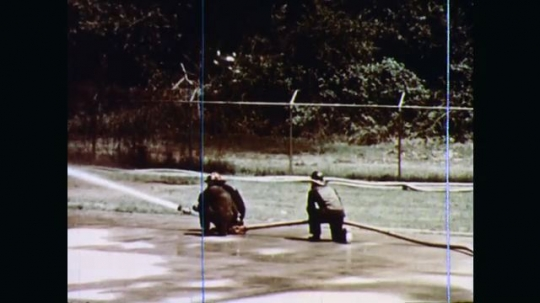 1970s: As tanks burn, firefighters mount hoses into holders planted in ground and retreat to safety. Flames spread around ground show fire hoses can spread burning fuel.