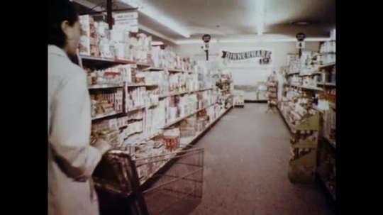 1960s: UNITED STATES: lady pushes trolley in supermarket aisle. Lady reads back of tin. Lady puts tin in cart.