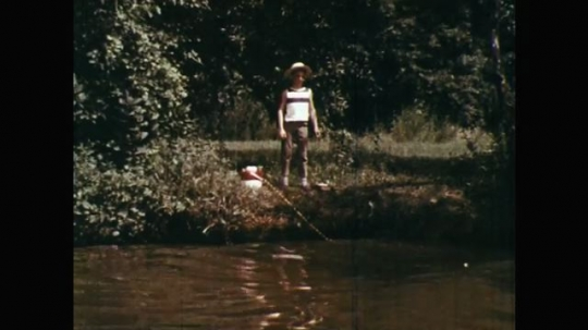 1960s: UNITED STATES: boy stands on river bank. Man stands on boat. Man falls in water. Man splashes