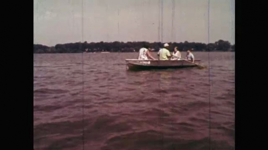 1960s: UNITED STATES: family on boat. Man rows boat on water. Children on boat