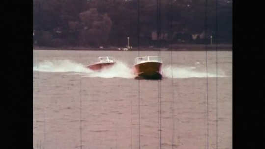 1960s: UNITED STATES: power boat speed across water. Man rows boat with family