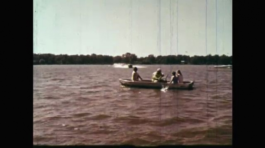1960s: UNITED STATES: speed boats rush towards rowing boat. Man stands on boat. Man falls in water. Girl runs to edge of land. Family help man in water