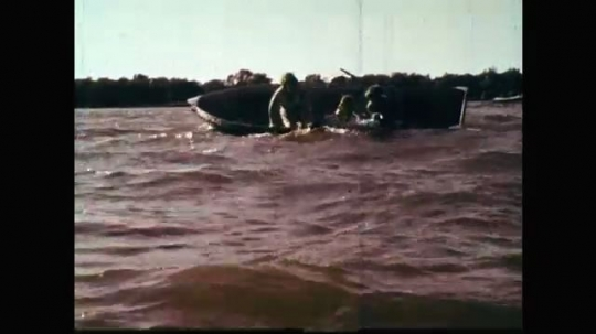 1960s: UNITED STATES: family tip boat over. Family in water. Girl on bank shouts for help. People disappear