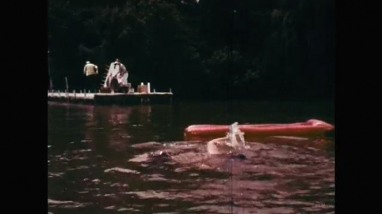 1960s: UNITED STATES: man sees girl drowning in water. Bag on floor