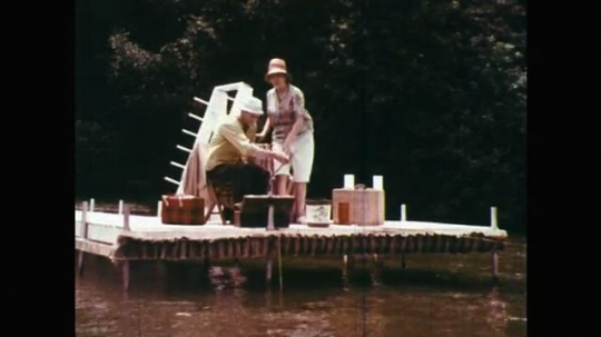 1960s: UNITED STATES: man puts down fishing rod. Man throws bag to girl. Man pulls girl to shore