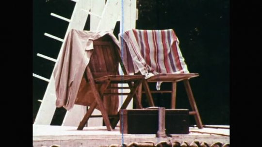 1960s: UNITED STATES: empty deck chairs. Man and lady pull girl from water. Man on fishing boat