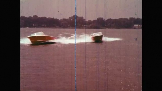1960s: UNITED STATES: speed boats race on water. Girl on river bank. Girl runs to car boot. Girl grabs tyre from car