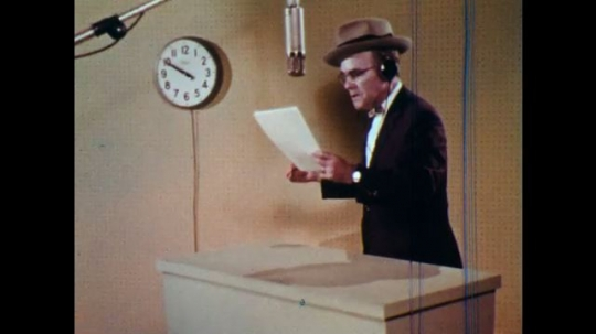 1970s: Man in recording booth holds paper and speaks into microphone. Man touches headphone and looks up.