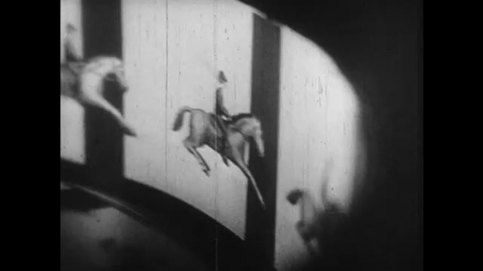 1920s: animated man rides horse inside a zeotrope. men dance in tight formation as indians. man hand cranks projector in movie theater. exploisions appear over battlefield.