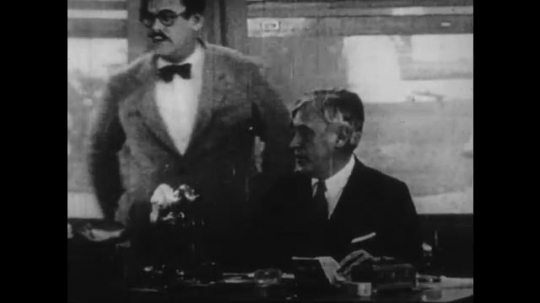 1920s: man rolls eyes and sits at desk while men rush around office. women cross city street corner. man brings women into office with girls, man and woman sit around table.