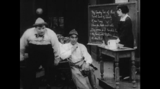 1920s: large fat man squeezes into desk chair in classroom with boys and girls. woman waves ruler and hits man in hat. man talks on candlestick telephone and fires gun in bed.