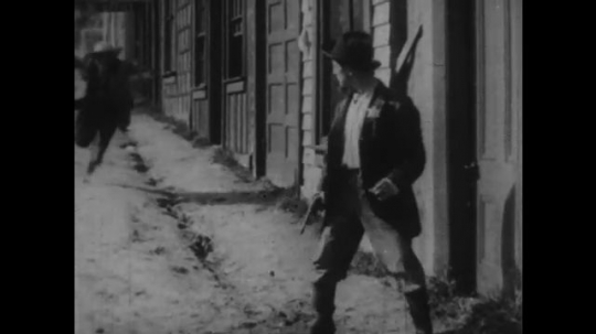 1920s: man rushes from door, trips and falls face first into dirt road. man with badge drives car out of police garage and backfires. men with guns gather by store.