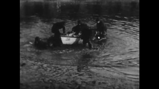 1920s: police flop on boat near shore. man speaks on candlestick telephone in field. cops grab ropes and run out of office. men  fire cannon on beach and fall over after blast.