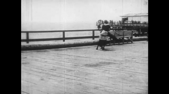 1920s: man in tuxedo and woman in maid outfit run around pier and fall down. old woman fires gun and police man jumps over fence. man talks on candlestick telephone. cop answers phone at station.