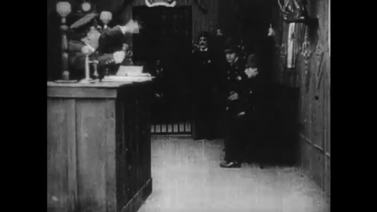 1920s: men in police station tumble, receive orders and run away. man in tuxedo and woman in maid uniform hide on pier. old woman waves and fire gun at ocean.