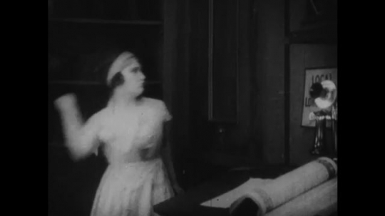 1920s: woman punches through door and hits man in tuxedo. man straps large necklace on woman