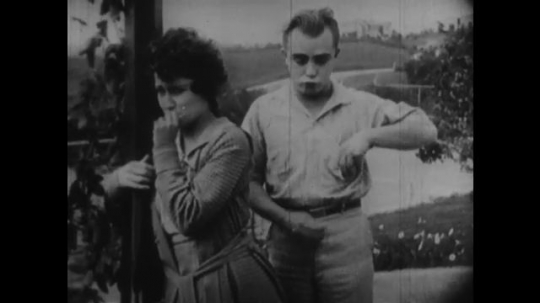 1920s: man hands ring to woman on porch. man and woman kiss her hand.
