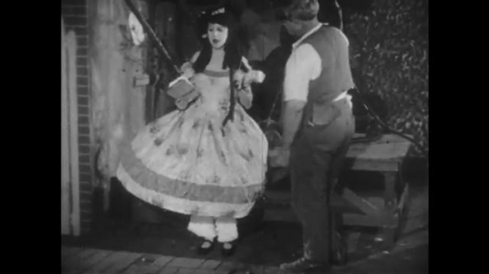 1920s: woman in huge dress takes books from man. men and women sit next to movie camera. man chews and spits out gum. man speaks into megaphone. woman stretches gum stuck on shoe.